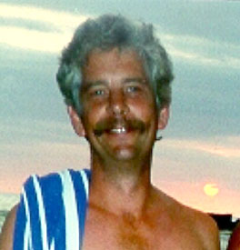 head photo of Kevin W. Krywe with blue and white stiped towel over right shoulder; sunset in background